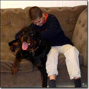 Rottie-Gabriel and KC happy petting Gabriel on couch